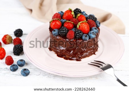 Tasty chocolate cake with different berries, on wooden table - stock photo