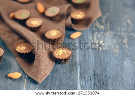 Tasty chocolate candies on napkin, on wooden table - stock photo