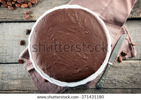Tasty chocolate frosting cake on wooden table - stock photo