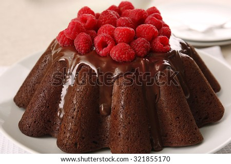 Tasty chocolate muffin with glaze and raspberries on table close up - stock photo
