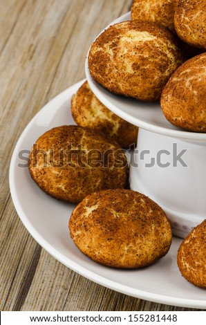 Tasty cinnamon cookies on white ceramic dish over wooden table.