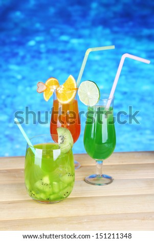 Tasty cocktails on swimming pool background