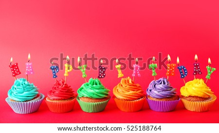 Tasty colorful cupcakes with Happy Birthday candles on red background