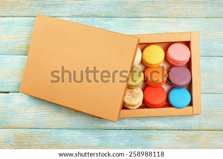 Tasty colorful macaroons in carton box on color wooden background - stock photo
