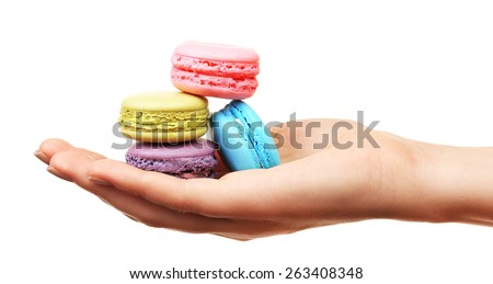 Tasty colorful macaroons in female hand isolated on white - stock photo