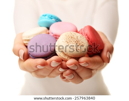 Tasty colorful macaroons in female hands on white background, closeup view - stock photo