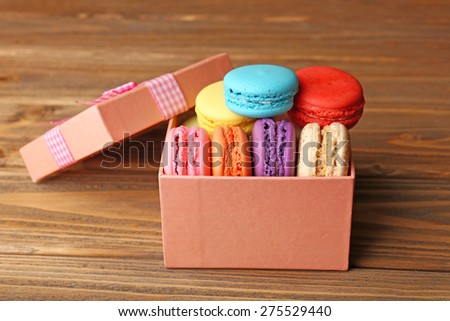 Tasty colorful macaroons in present box on rustic wooden planks background - stock photo