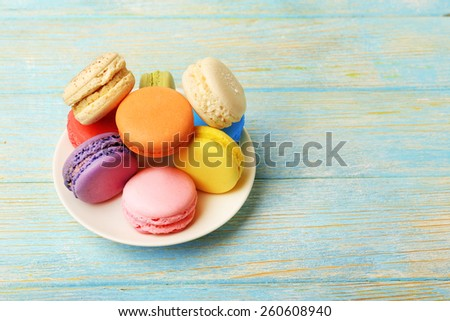 Tasty colorful macaroons in small plate on color wooden background - stock photo
