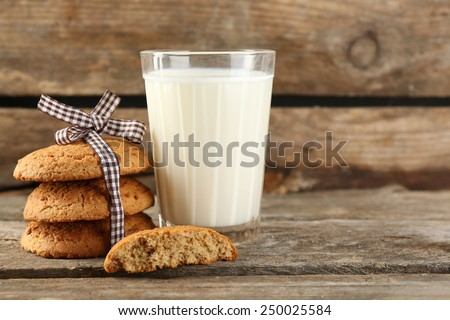 Tasty cookies and glass of milk on rustic wooden background - stock photo