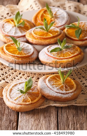 Tasty cookies with oranges, decorated with mint and powdered sugar close-up on a plate. Vertical