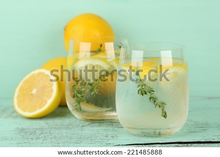 Tasty cool beverage with lemon and thyme, on wooden background - stock photo