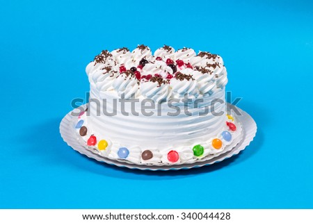 Tasty creamy birthday cake colorful candy adorned on blue background - stock photo