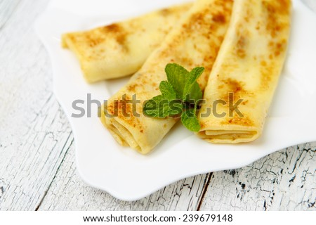 Tasty crepes on wooden table studio shot
