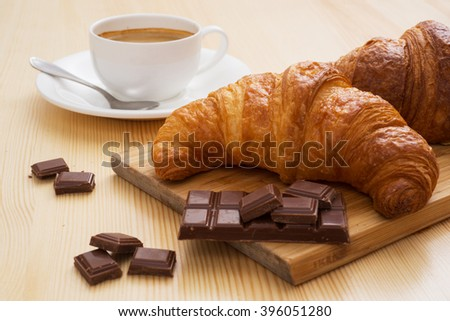 Tasty croissant with chocolate and cup of coffee