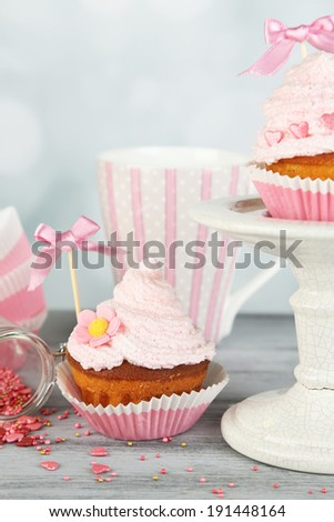 Tasty cup cakes with cream on grey wooden table