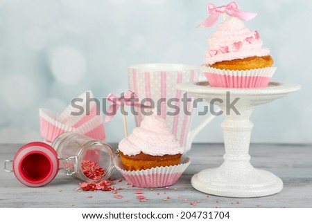 Tasty cup cakes with cream on grey wooden table - stock photo