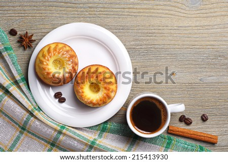 Tasty cupcake and cup of coffee on table covered with a tablecloth. Top view - stock photo