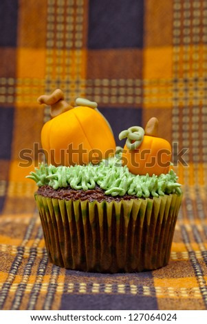 Tasty cupcake decorated with pumpkin miniature and displayed on a table cloth. - stock photo