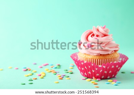 Tasty cupcake on green background - stock photo