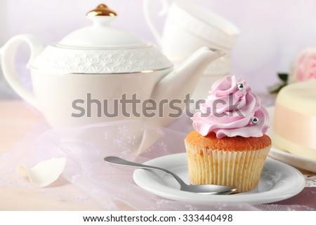 Tasty cupcake on saucer, on light background - stock photo