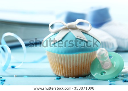 Tasty cupcake with bow and baby shoes on color wooden background - stock photo