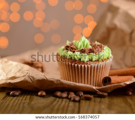 Tasty cupcake with butter cream, on wooden table, on lights background