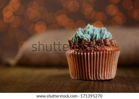 Tasty cupcake with butter cream, on wooden table, on lights background - stock photo