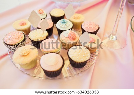 Tasty cupcakes covered with pink glaze stand on glass plate