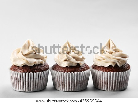 Tasty cupcakes on light background