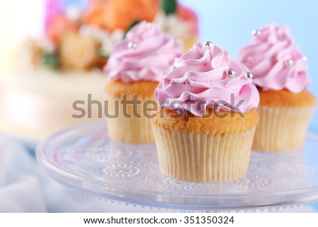 Tasty cupcakes on stand and cake, on table, on color background - stock photo