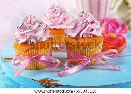 Tasty cupcakes on tray, on light background - stock photo