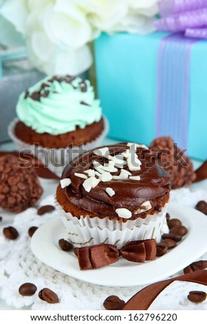 Tasty cupcakes with gifts close up - stock photo