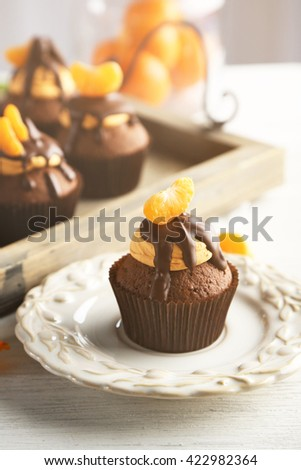 Tasty cupcakes with slice of mandarin and chocolate on a tray over light wooden background - stock photo
