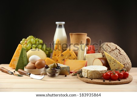 Tasty dairy products on wooden table, on dark background - stock photo