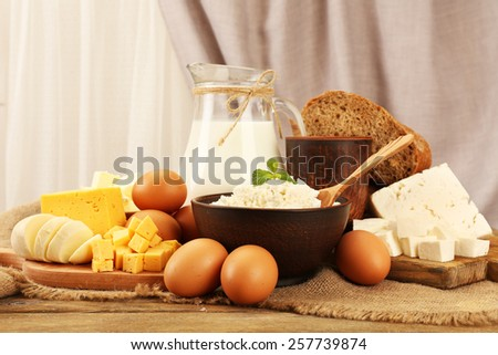 Tasty dairy products with bread on table on fabric background - stock photo