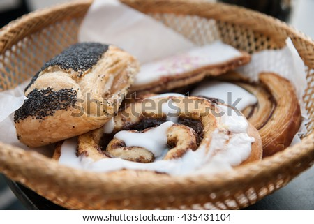 Tasty Danish pastry and cakes in a basket, on a table, stock picture - stock photo