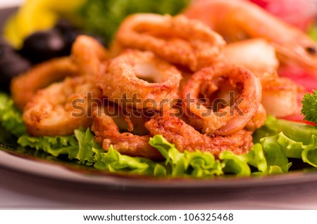 Tasty deep fried squid rings with vegetables - stock photo
