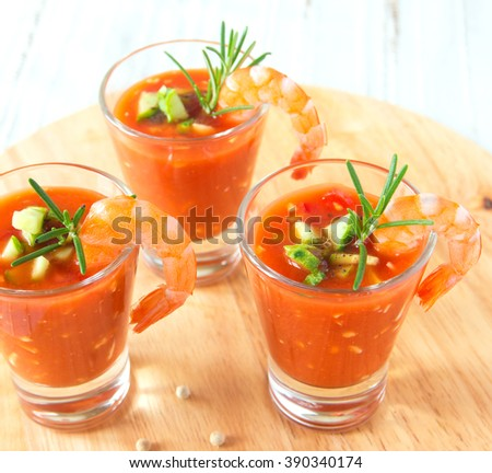 Tasty delicious fresh cold vegetable tomato soup with shrimps and rosemary in portion glasses on wooden board close up, horizontal. Party appetizer. - stock photo