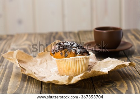 Tasty delicious muffin in white form decorated by chocolate chips powdered sugar on pack paper and beautiful brown cup of strong aroma coffee on saucer sweet breakfast cafe studio closeup, horizontal  - stock photo