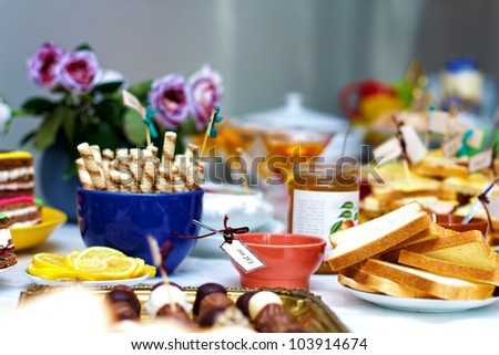 tasty delicious of English tea party, with fresh fruits, jam, biscuits and sandwiches - stock photo