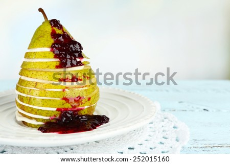 Tasty dessert with sliced pear, cream and berry sauce on plate, on wooden table, on light background - stock photo