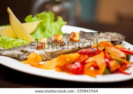 Tasty dish of rainbow trout fish with vegetables - stock photo