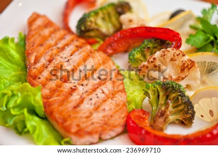 Tasty dish of salmon steak with vegetables and juice - stock photo
