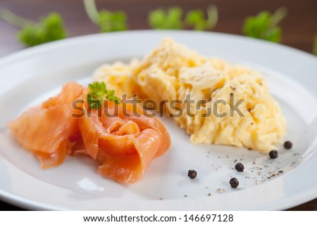 Tasty dish of salmon with scrambled eggs - stock photo