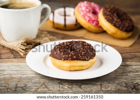 tasty donut with nut-chocolate topping and  fresh brewed coffee - stock photo