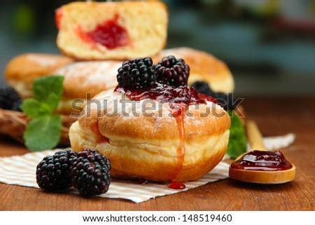 Tasty donuts with berries on wooden table - stock photo