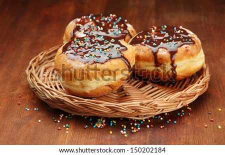 Tasty donuts with chocolate on wooden table