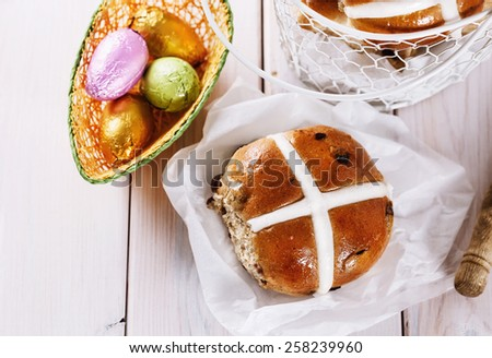 Tasty Easter cross-bun and chocolate Easter eggs on white wooden background close up. Selective focus - stock photo