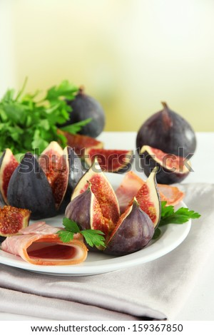Tasty figs with ham on table - stock photo