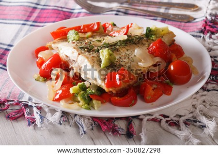 Tasty flounder with seasonal vegetables close-up on a plate. horizontal